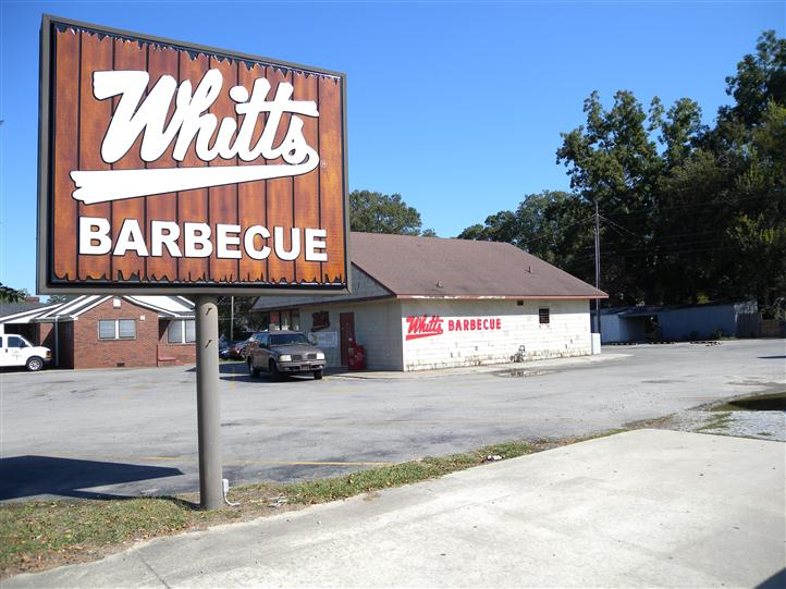 "large sign in the parking lot that reads, ""Whitts Barbeque"""