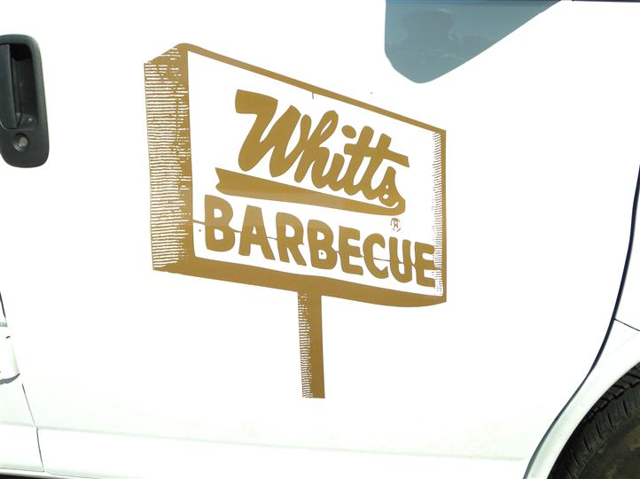 the Whitts Barbeque logo, painted on the side door of their van