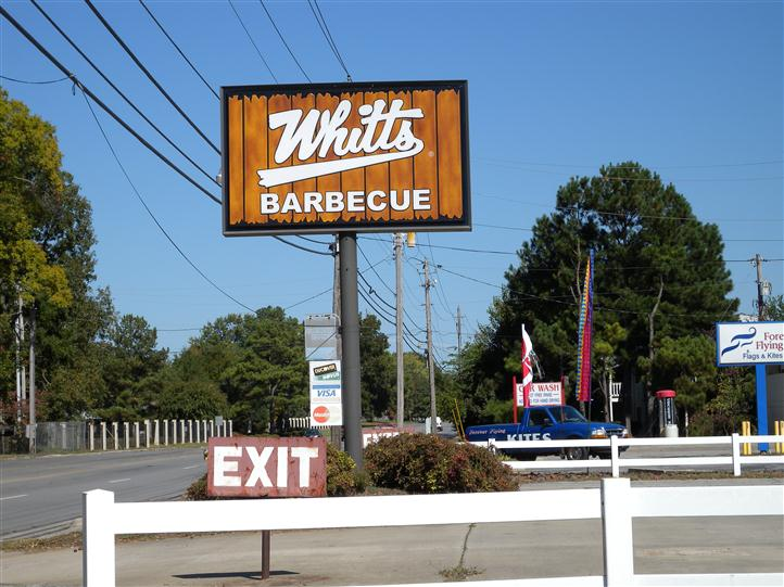 Whitts Barbeque sign in the parking lot, next to the parking lot exit sign