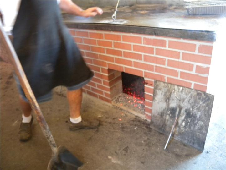 an employee filling the furnance with wood