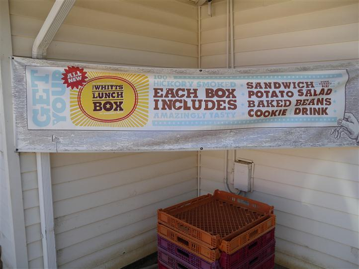 "a banner that reads, ""Get your Whitts Lunch Box - Each box includes 100% hickory smoked, amazingly tasty sandwich, potato salad, baked beans, cookie, and drink"""