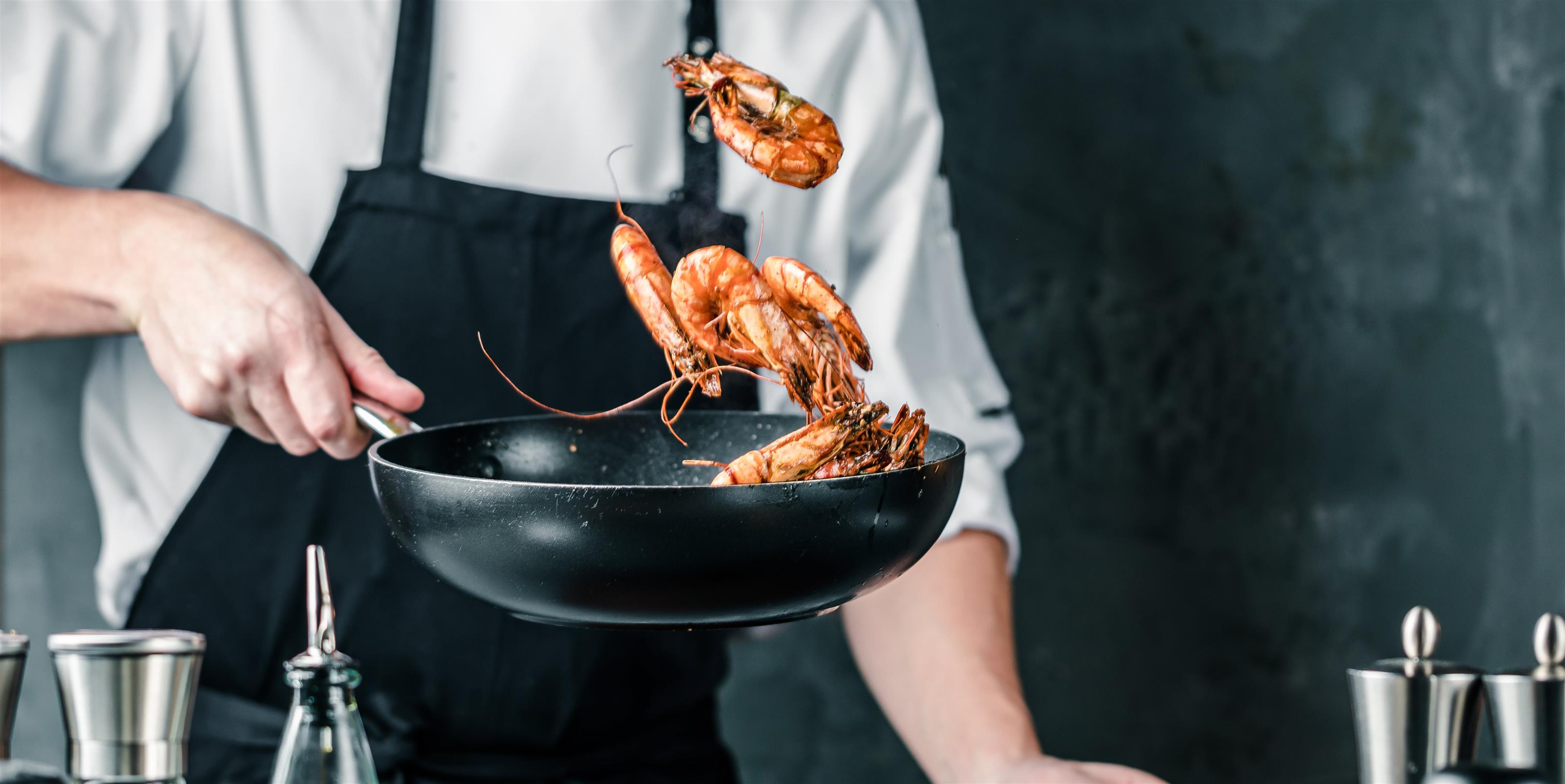 chef tossing shrimp in a pan