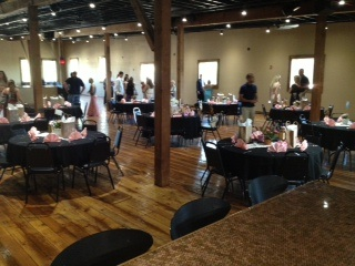 photo of a private party with round tables and gifts on all the tables, in an open space
