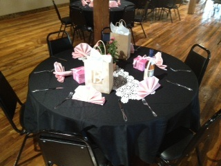 table with gifts on it and a black table cloth with silverware around