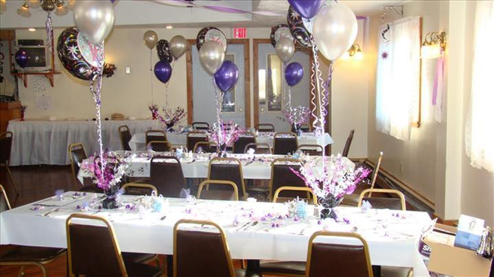 Private hall set for a special occasion with the tables decorated with white and purple balloons and flower centerpieces