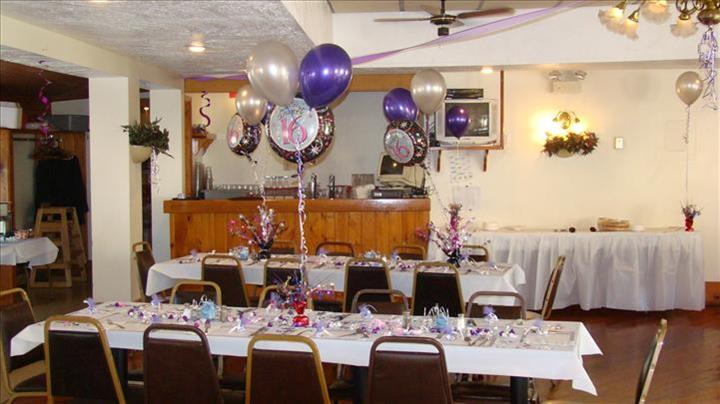 Private hall set for a special occasion with the tables decorated wprivate hall set for a special occasion with the tables decorated with white and purple balloons and flower centerpieces and a bar counter in the background