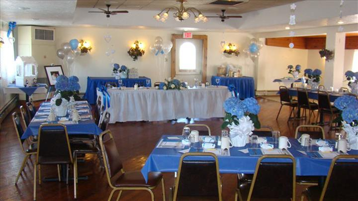 Private hall set for a special occasion with the tables decorated in blue linen and flowers