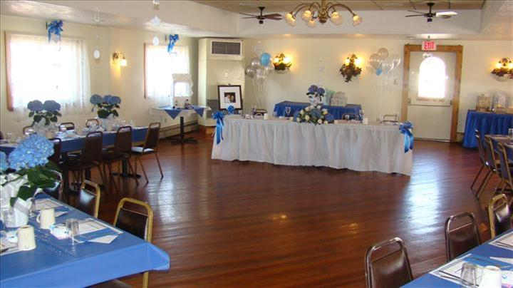Main table in the center of a private hall set for a special occasion with blue and white decorations