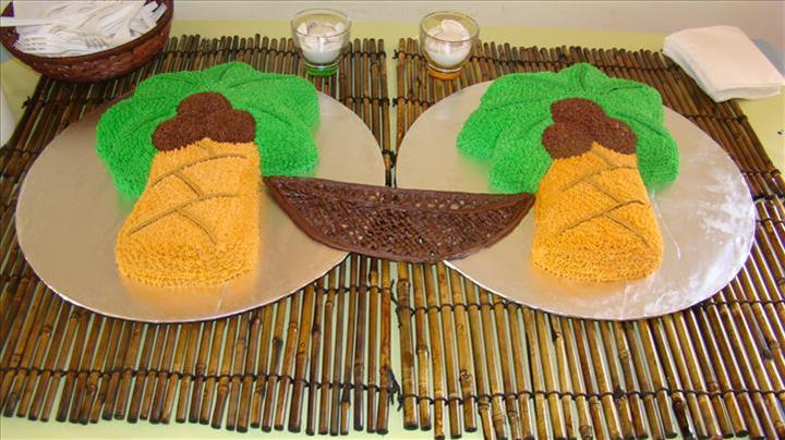 Special cake in the shape of two coconut trees and a rope hammock hanging between them set on bamboo place mats