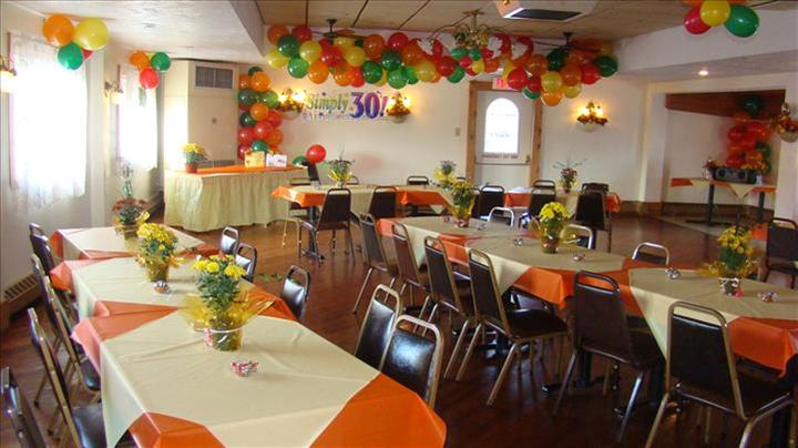 Private room for special events decorated with colorful balloons and tables set with orange and yellow linen with flower center pieces