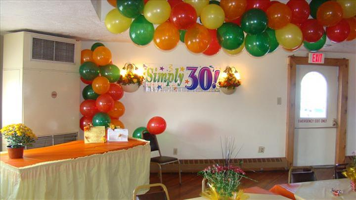 Green, yellow, orange and red balloon-formations decorating the ceiling, birthday banner on the wall and a table set eith presents on top in a room decorated for a special occasion