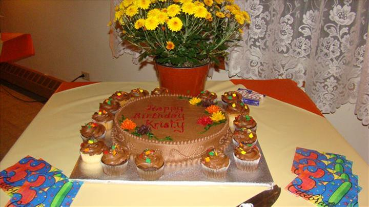 Chocolate birthday cake decorated with chocolate frosting and colorful flower rosettes surrounded with chocolate cupcakes on a table wih colorful napkins and a small flowerpot with yellow flowers