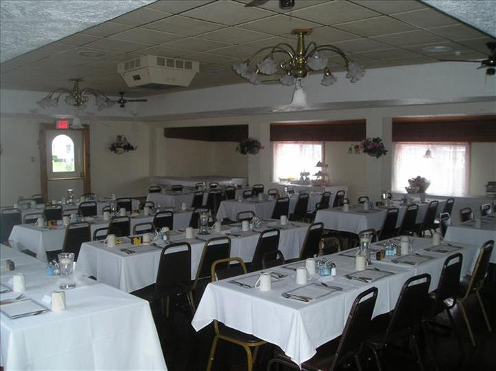Dining hall with tables set in white linen