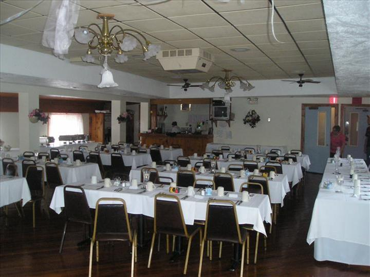 Dining hall with tables set in white linen and the bar in the background