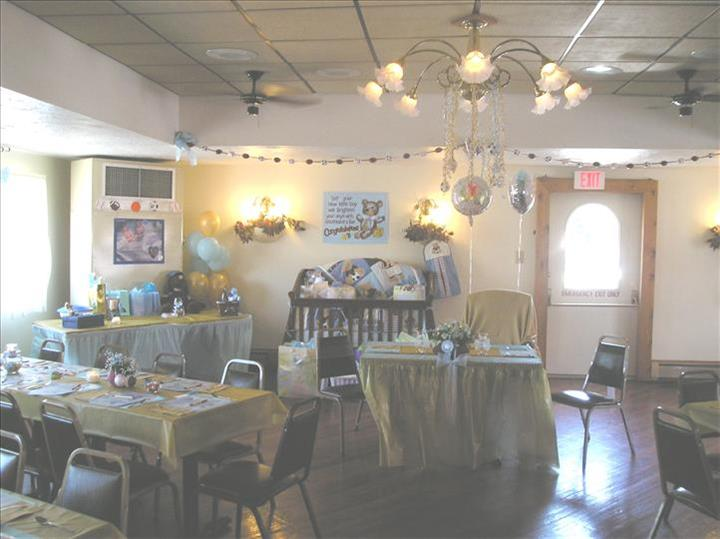 Event room decorated for a baby shower with colorful tables set for a party, a buffet table covered with presents and a baby cot in the background decorated with colorful presents