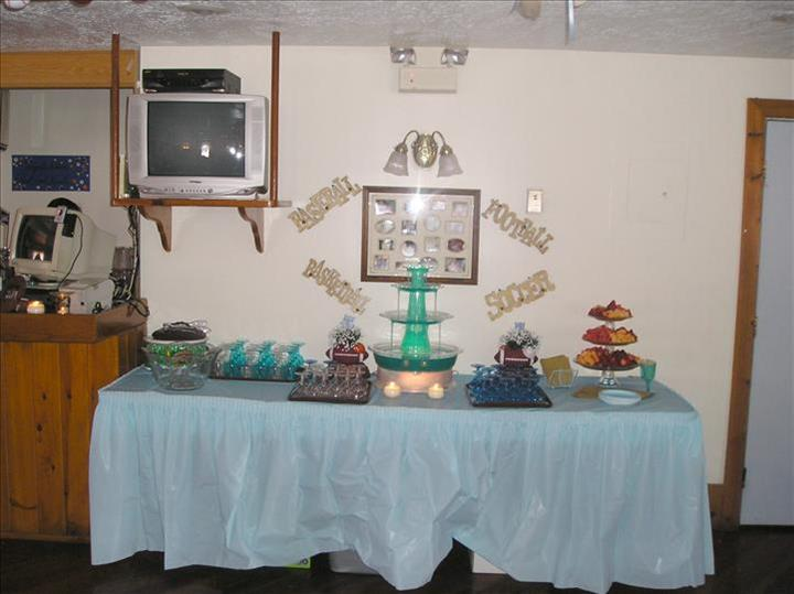 Buffet table with blue linen set with cake stands and snack platter and glasses and drinks for a special event