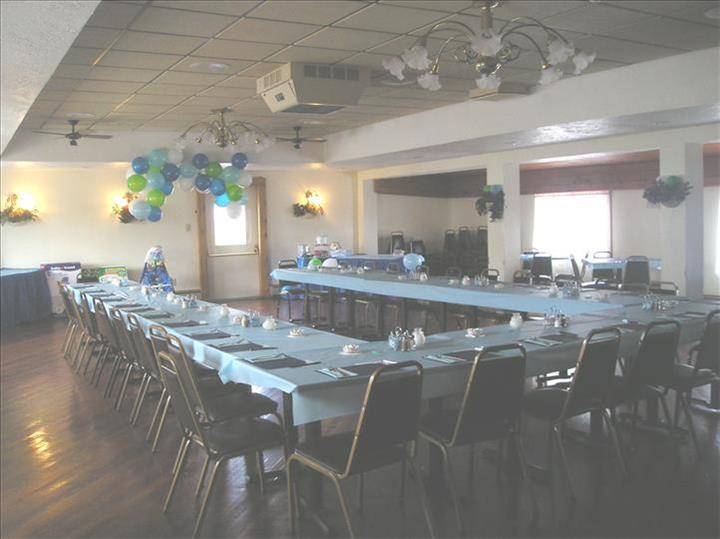 Event room with tables in light blue linen set for a special occasion and decorated with blue and green balloons