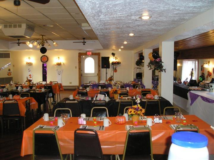 Dining hall with tables set for Halloween in orange linen, tables decorated with pumpkins and and fall flowers and balloons and flower decorations on the wall