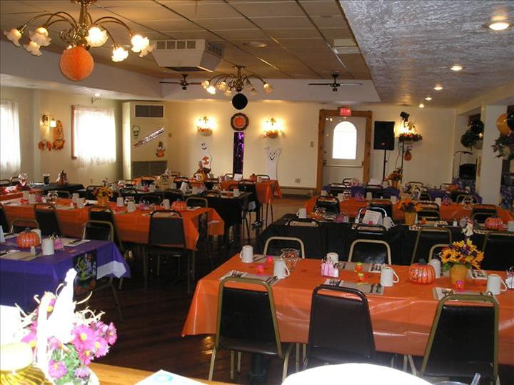 Dining hall with tables set for Halloween in orange and purple linen, tables decorated with pumpkins and and fall flowers and balloons and flower decorations on the wall
