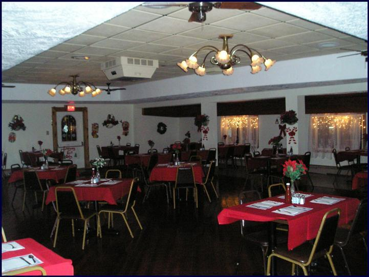 Dining hall set for dinner with tables covered in red linen with red roses in the center of the table tops