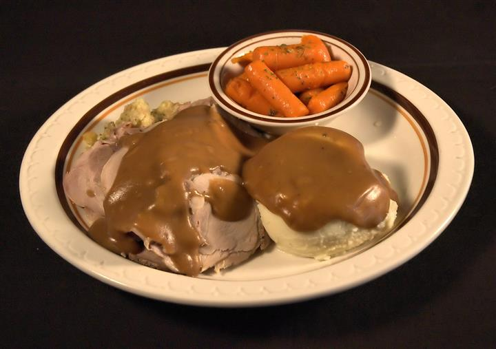 Roast beef dinner smothered with brown gravy and served with mashed potatoes and a side of roasted carrots