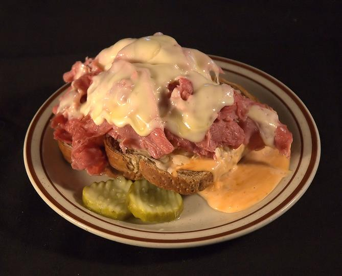 Open faced Reuben sandwich with thinly sliced corned beef, Russian dressing and Swiss cheese grilled on rye bread