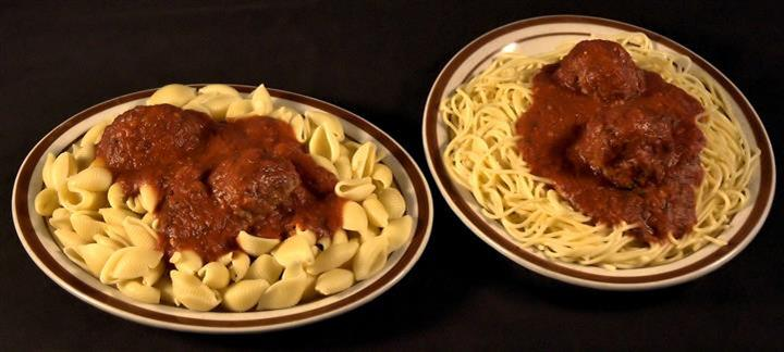Two plates of pasta. A plate of shells and a plate of spaghetti both topped with two meatballs in marinara sauce