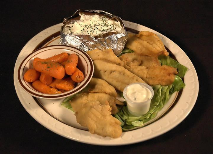 Fried lake perch pieces served with a jacket potato wrapped in foil and a side of baby carrots with a dipping sauce