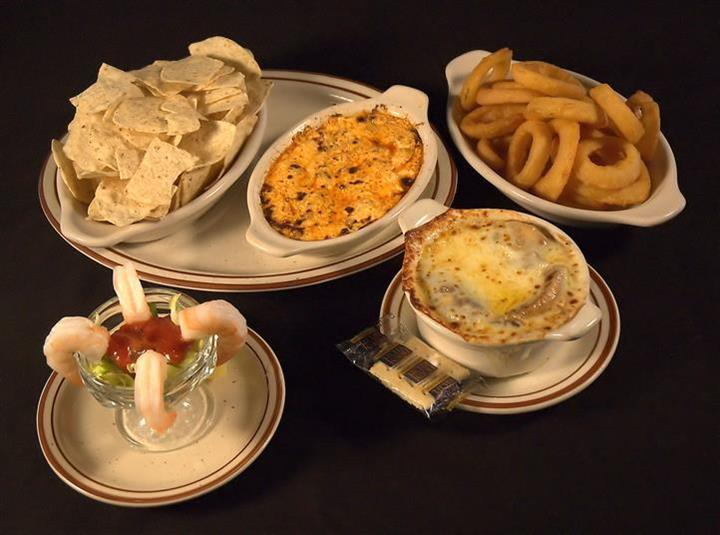 Variety of plates with appetizers. Chicken wing dip with tortilla chips in a platter next to a plate of fried onion rings, a tall glass of shrimp cocktail and soup with melted cheese in a bowl