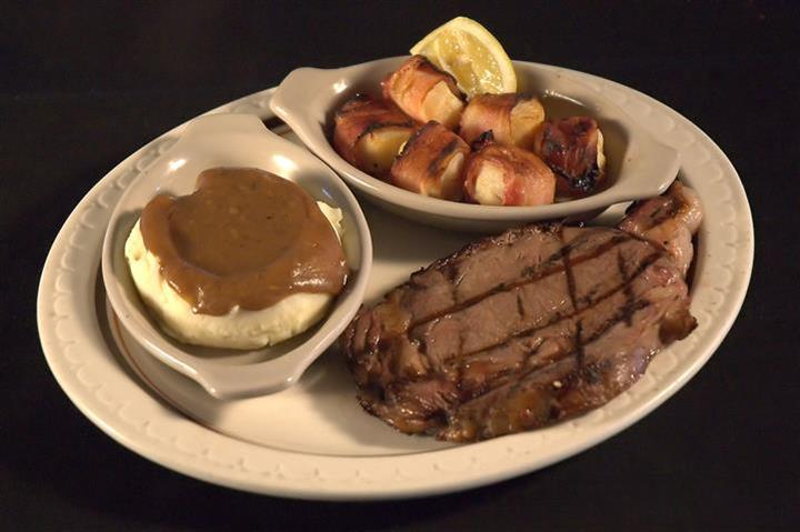 Grilled steak served with a side of bacon wrapped scallops and a side of mashed potatoes served with brown gravy