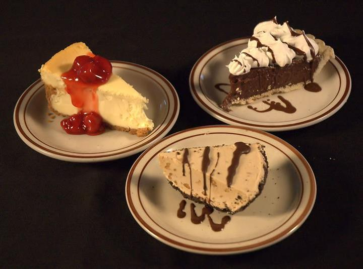 Variety of small plates with pies and cakes. A piece of cheesecake topped with cherries, a plate of peanut butter pie and a plate of chocolate cream pie