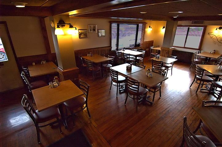 Interior shot of the dining tables, the wooden floors and the lighting fixtures on the wall