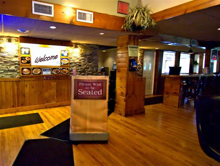 Restaurant entryway with welcome sign on the wall and waiting area
