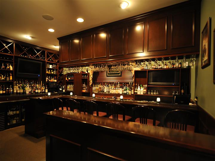 interior bar area with stools, liquor bottles and wine glasses hanging upside down