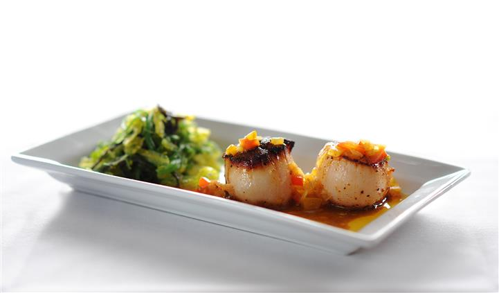 cooked scallops with sauce and vegetable