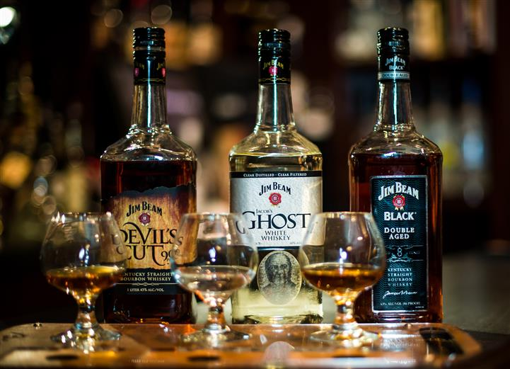 three whiskey bottles and glasses of jim beams devils cut, ghost and black