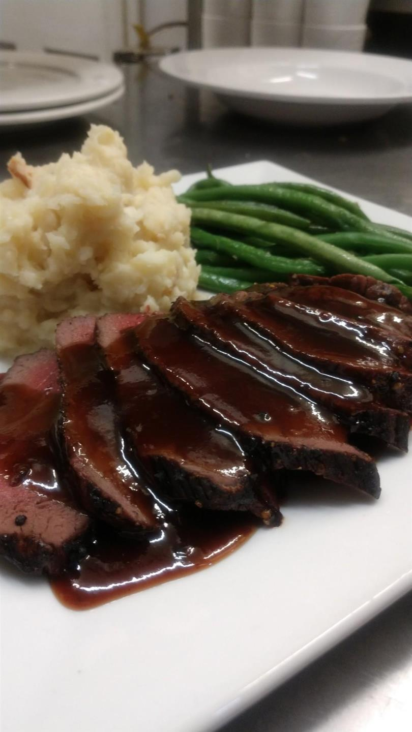 Venison Loin with mashed potatoes and string beans on plate