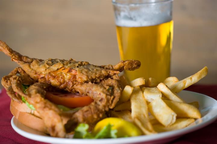 fried blue crab on a roll with a side of fries and a beer