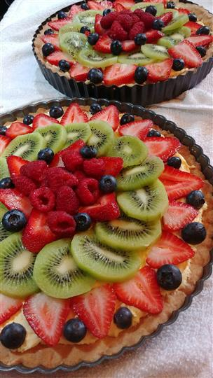 large dessert pie covered in sliced fruit