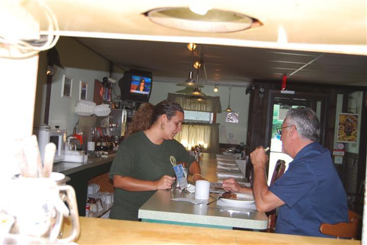 waitress at the counter taking an order from a customer
