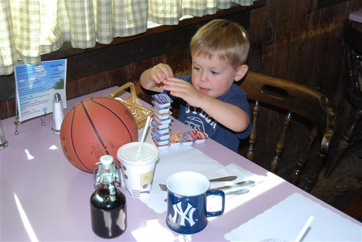 young boy eating at the table stacking together the individual jams together
