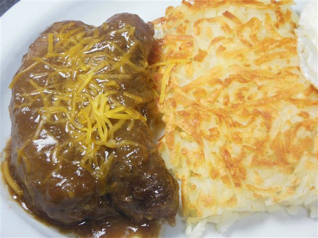 two sauasage links in sauce with hash browns