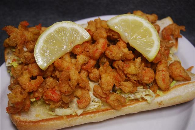 popcorn shrimp on a roll with lemon wedges