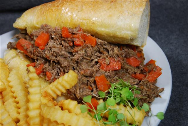 pulled pork sandwich with peppers and a side of french fries