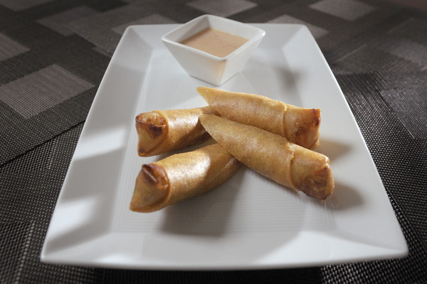 four fried egg rolls on a plate with dipping sauce