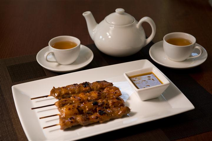 chicken skewers on a plate with dipping sauce with a pot of tea and cups