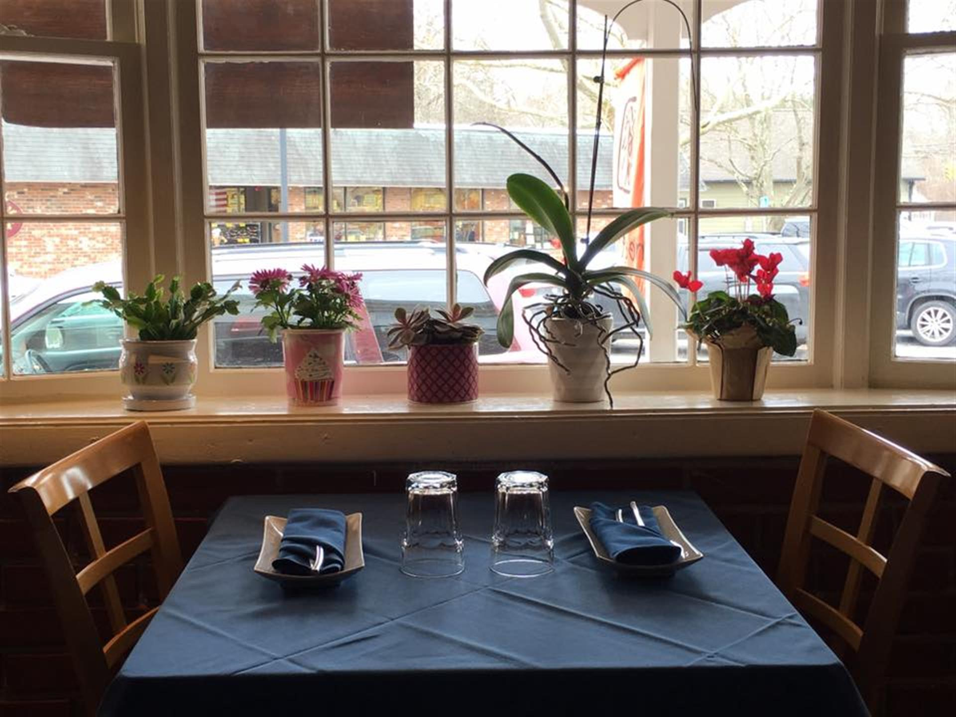table next to a window with flowers in the window