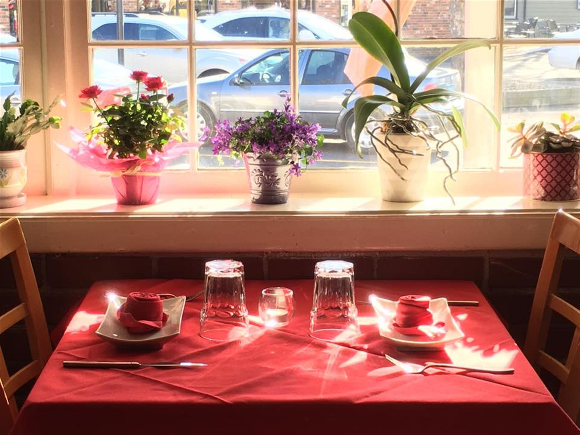 table next to a window. table has plates, silverware, wine glasses. flowers are in the window.