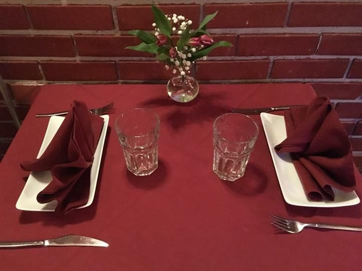 dining table setup with cups, plates, utensils and napkins