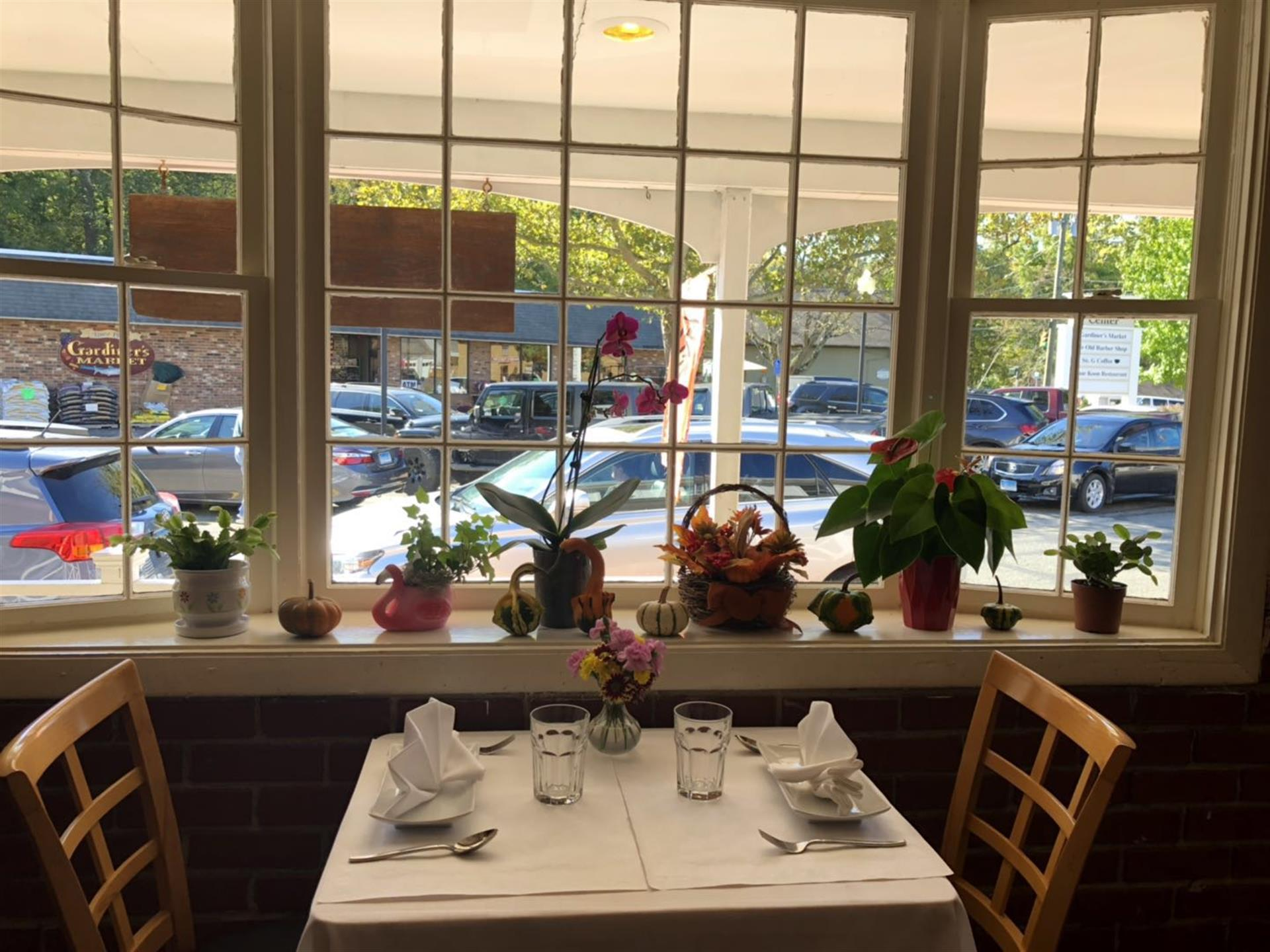 table next to a window. table has plates, silverware, water glasses. flowers are in the window.